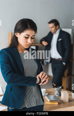 Businesswoman checking watch while man in business suit standing by shelves in light office - Stock Photo