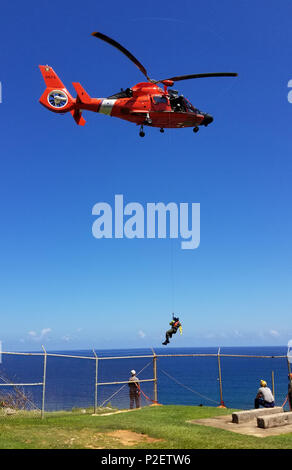 Coast Guard helicopter crews conducted cliff and vertical surface rescue training Sept. 15, 2016, near Air Station Borinquen, 200 feet above Survivor Beach, in Aguadilla, as part of crew certification requirements to conduct search and rescue operations in Puerto Rico and the U.S. Virgin Islands. (U.S. Coast Guard photo by Lt. Matt Udkow, Air Station Borinquen MH-65 Dolphin helicopter pilot). - Stock Photo