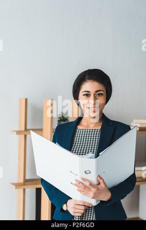 Smiling businesswoman holding folder in modern office - Stock Photo