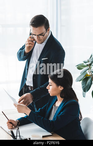 Businessman talking on phone and looking at papers in businesswoman hands - Stock Photo