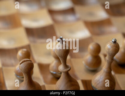 Carved wooden chessmen with focus on king - Stock Photo