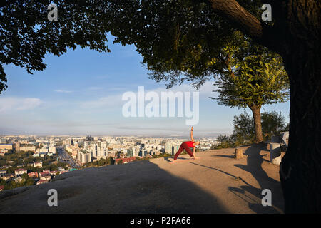 Fit man in red costume doing yoga triangle asana in the park with city and mountain on background in Almaty, Kazakhstan - Stock Photo