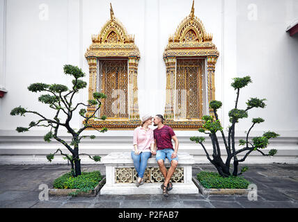 Young Couple in red clothes sitting on the bench near decorative trees and golden windows of Wat Pho in Bangkok, Thailand - Stock Photo