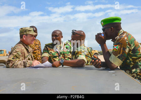 U.S. Army Capt. Mike Smith, left, Combined Joint Task Force - Horn of Africa Military Coordination Cell logistics representative, reviews an item list with Capt. Ndikumana, center right, Burundi National Defense Force African Union Mission in Somalia Burundi contingent team leader, in Mogadishu, Somalia, Sept. 12, 2016. Burundi forces received more than 10 power generators, tires and spare parts for Mine Resistant Ambush Protected vehicles to remedy the wear and tear on vehicle parts caused by rough and uneven terrain. The MRAP vehicles are vital to keeping AMISOM forces safe from roadside bom - Stock Photo