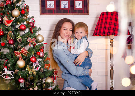 Young caucasian mother standing with little daughter near christmas tree. - Stock Photo