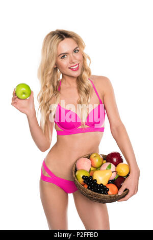 beautiful blonde woman in pink bikini holding apple and basket with fruits, isolated on white - Stock Photo