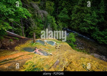 A woman relaxes in the scenic Umpqua hot springs in the mountains above the North Umpqua River in southern Oregon. - Stock Photo