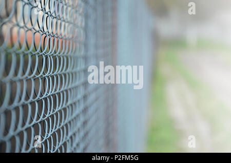 A photograph of a metal net used as a fence of private possessions. Old metal grid in perspective with a blurred background - Stock Photo