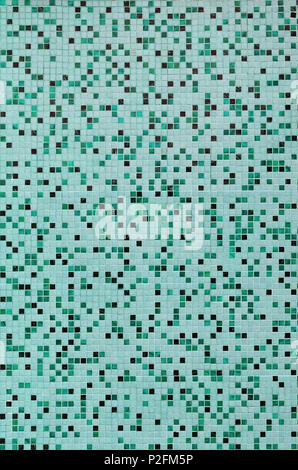 The texture of the wall, decorated with a mosaic of various small square tiles. Abstract pattern of ceramic tiles on the wall - Stock Photo
