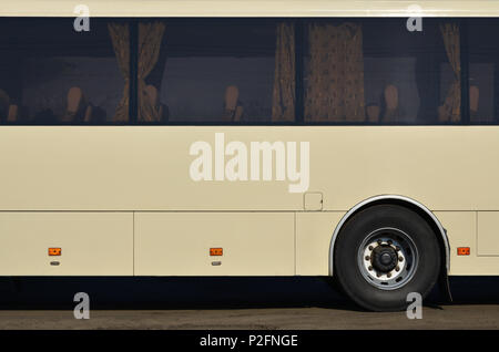 Photo of the hull of a large and long yellow bus with free space for advertising. Close-up side view of a passenger vehicle for transportation and tou - Stock Photo