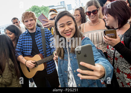 London, UK. 14th June 2018. Madame Tussauds unveil Ed Sheeran waxwork model at Wembley Park station for photo-selfies with locals including police officers. Credit: Guy Corbishley/Alamy Live News - Stock Photo
