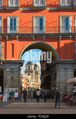 Madrid architecture city center, view south through the 17th century Arco Toledo in the Plaza Mayor towards the Iglesia Colegiata de San Isidro, Spain. - Stock Photo