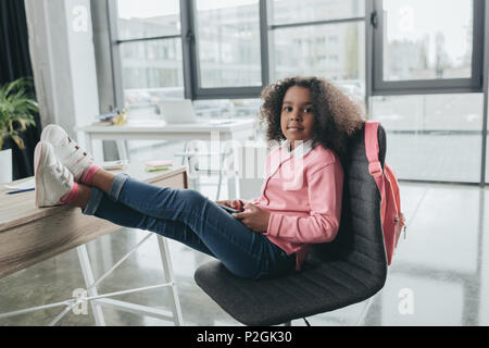 little african american girl sitting on chair with legs on table in modern office - Stock Photo