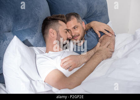 Happy gay couple lying embracing in bed and smiling each other - Stock Photo