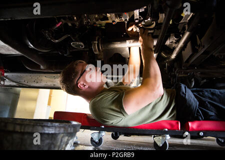 Lance Cpl. Gordon Budd fixes the oil pan on a Humvee while conducting routine maintenance at Camp Lejeune, N.C., Sept. 13, 2016. Marines with 2nd TSB provide continuous maintenance on transport vehicles to help maintain the capabilities and operations of 2nd Marine Logistics Group. Budd is a motor transportation mechanic with 2nd TSB. (U.S. Marine Corps photo by Sgt. Anthony Mesa/Released) - Stock Photo