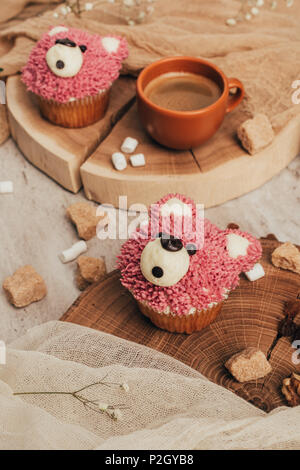 close-up view of delicious sweet cupcakes in shape of bears and cup of coffee on table - Stock Photo
