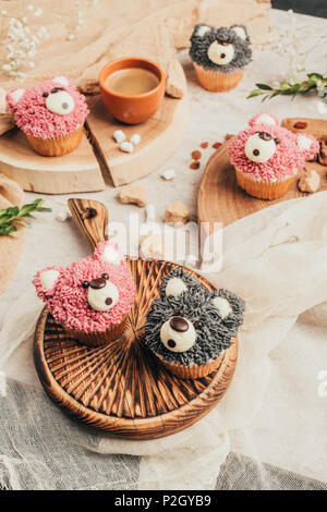 close-up view of delicious sweet cupcakes in shape of bears on table - Stock Photo