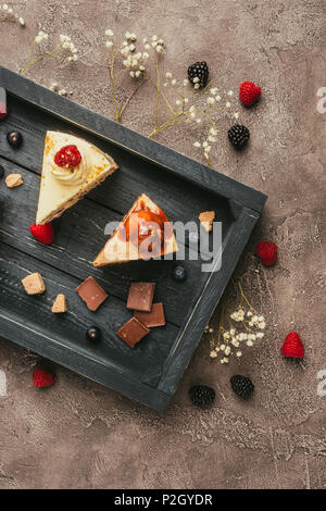 top view of sweet tasty cakes with chocolate and berries on wooden tray - Stock Photo