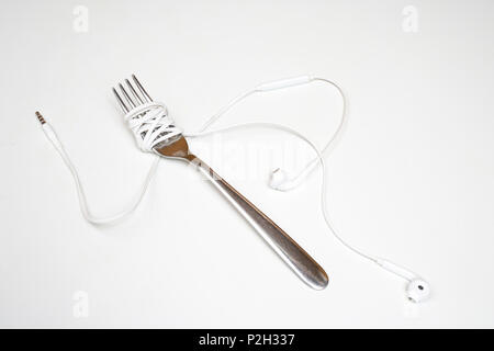 the headphones wrapped up a fork on a white surface - Stock Photo