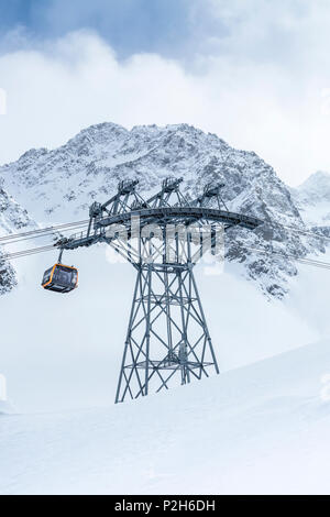 Gondola of cableway at Stubai Glacier ski resort with snowy mountains as background, Neustift im Stubaital, Austrian Alps, Tyrol, Austria - Stock Photo
