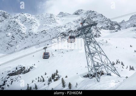 Gondolas of cableway at Stubai Glacier ski resort with snowy mountains as background, Neustift im Stubaital, Austrian Alps, Tyrol, Austria - Stock Photo