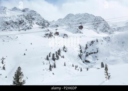 Gondolas of cableway at Stubai Glacier ski resort with snowy mountains as background, Neustift im Stubaital, Austrian Alps, Tyrol, Austria - Stock Photo