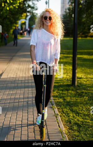 Photo of curly-haired athletic woman riding scooter in park on summer day - Stock Photo