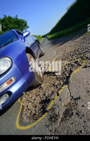 car driving over enormous pot hole on road marked with yellow outline for repair,york yorkshire unitedc kingdom - Stock Photo