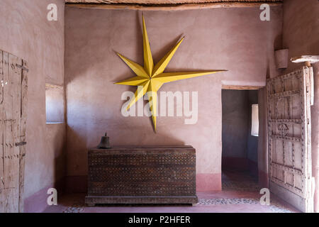 Large yellow star hung on earth wall in entrance hall of Berber Lodge with antique wooden chest and studded panelled door - Stock Photo