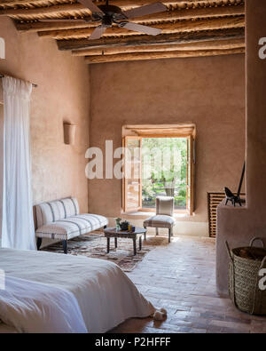 Old moroccan tea table in seating area in bedroom with earth walls, terracotta floor and traditional berber wood ceiling - Stock Photo