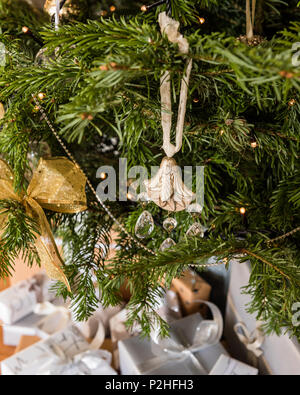 baubles, stars, fairy lights and bows adorn a chirstmas tree - Stock Photo