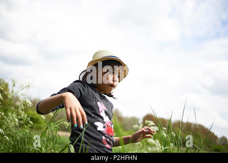 Two young Asian sisters walking on a small path in a forest surrounded by high grass in spring sunshine - Stock Photo