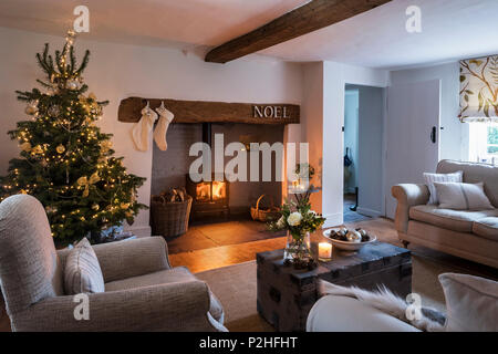 Cosy festive sitting room with inglenook fireplace and christmas tree, the sofa is by Laura Ashley and the blind in Lewis & Woods Adam's Eden fabric - Stock Photo