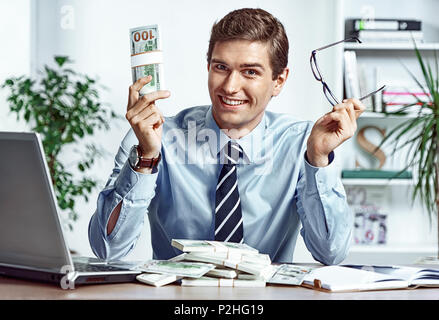 Successful businessman takes off his glasses and showing money. Photo of young man working in the office. Business concept - Stock Photo