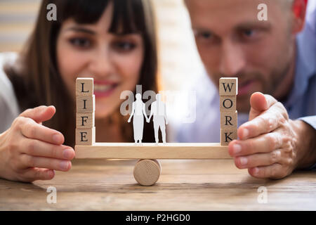 Happy Couple Protecting Balance Between Work And Life With Family Paper Cut Out On Seesaw - Stock Photo