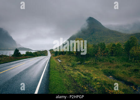 Scenic road along the coastline in Norway on a rainy and foggy day - Stock Photo