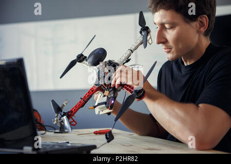 Photo of engineer fixing copter and sitting at table with laptop - Stock Photo