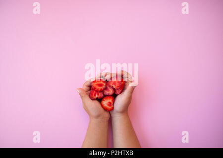 Child's hands holding beautiful fresh juicy strawberries on pastel pink background with text space. - Stock Photo