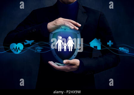 Concept For Insurance Company to Safe and Support thire Customer, Family icon inside a Shield Guard. Protected by Hands of Businessman - Stock Photo