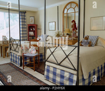 Blue+white checked valences on twin metal-framed beds in light and airy children's coastal bedroom - Stock Photo