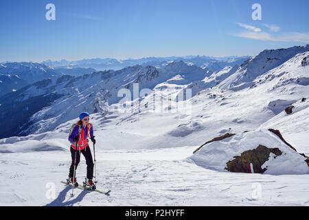 Woman back-country skiing ascending towards Schneespitze, Schneespitze, valley of Pflersch, Stubai Alps, South Tyrol, Italy - Stock Photo