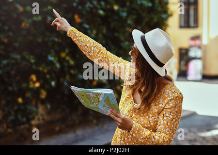 Smiling young brunette woman holding a map and pointing at sights while exploring the cobblestone streets of a city - Stock Photo