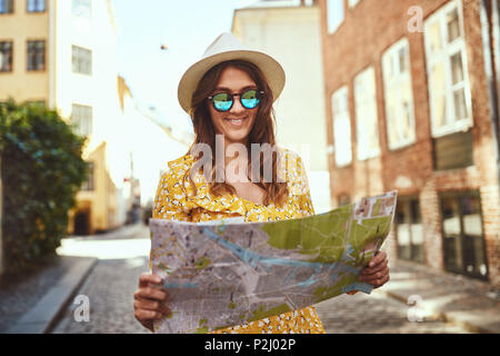 Smiling young brunette woman exploring the cobblestone streets of a city wearing sunglasses and a fedora reading a map - Stock Photo