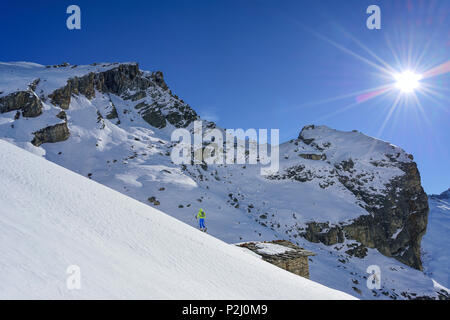 Woman back-country skiing ascending towards Monte Salza, crossing alpine hut, in background Rocca Senghi, Monte Salza, Valle Var - Stock Photo