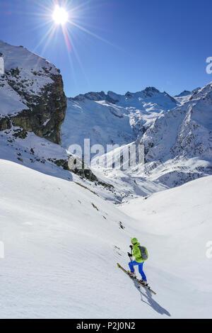 Woman back-country skiing ascending towards Monte Salza, in the background Rocca Senghi, Monte Salza, Valle Varaita, Cottian Alp - Stock Photo