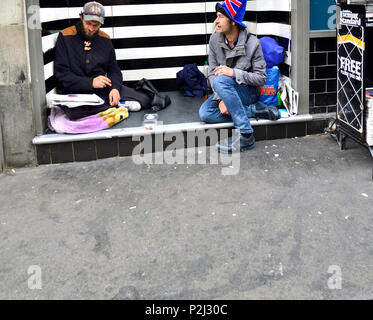 Two homeless men sitting in a doorway, the Strand, London, England, UK. - Stock Photo