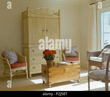Cream bamboo secretaire cabinet and pine chest in corner of sunlit bedroom with cane armchairs with floral cushions - Stock Photo