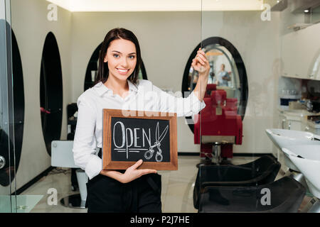 smiling owner of hair salon standing with sign open and leaning on glass door - Stock Photo