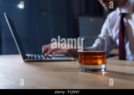 cropped image of businessman working at laptop with glass of whiskey on foreground - Stock Photo