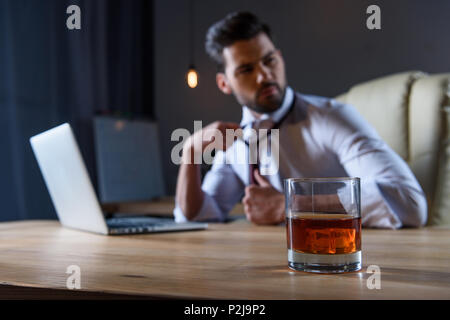 tired businessman loosen tie and sitting at table with glass of whiskey on foreground - Stock Photo
